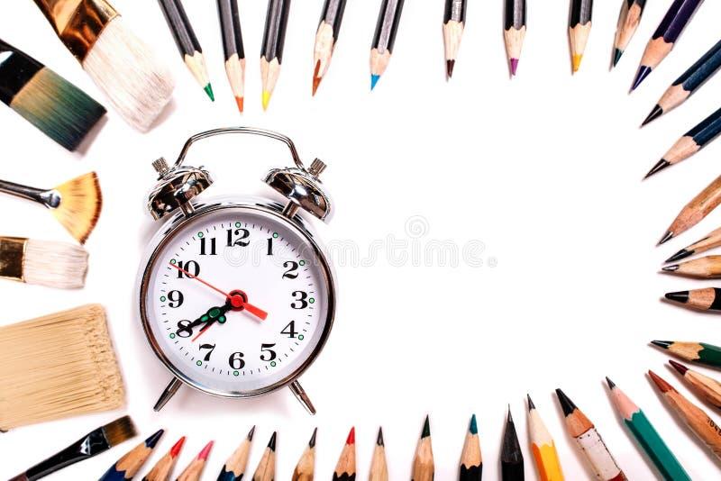 Покрашенные карандаши с tassels изолированными на белой предпосылке Выровнянный в форме овальной рамки с космосом будильника для  стоковые фотографии rf