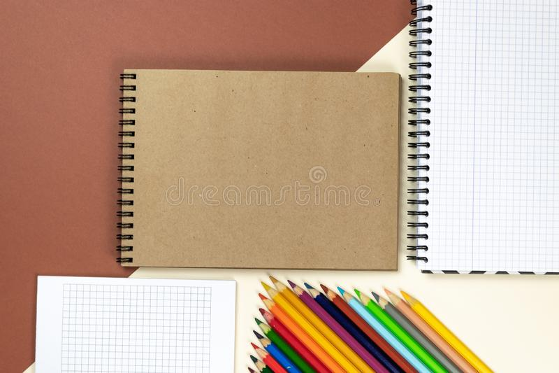 Покрашенные карандаши, тетради на коричневой и бежевой предпосылке Клеймя сцена модель-макета канцелярских принадлежностей, пусты стоковая фотография rf