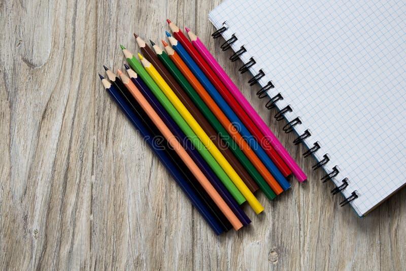 Покрашенные карандаши налево блокнота на деревянной предпосылке стоковые фото