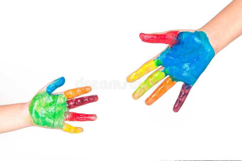 Покрашенные красочные руки ребенк на белой предпосылке стоковое фото