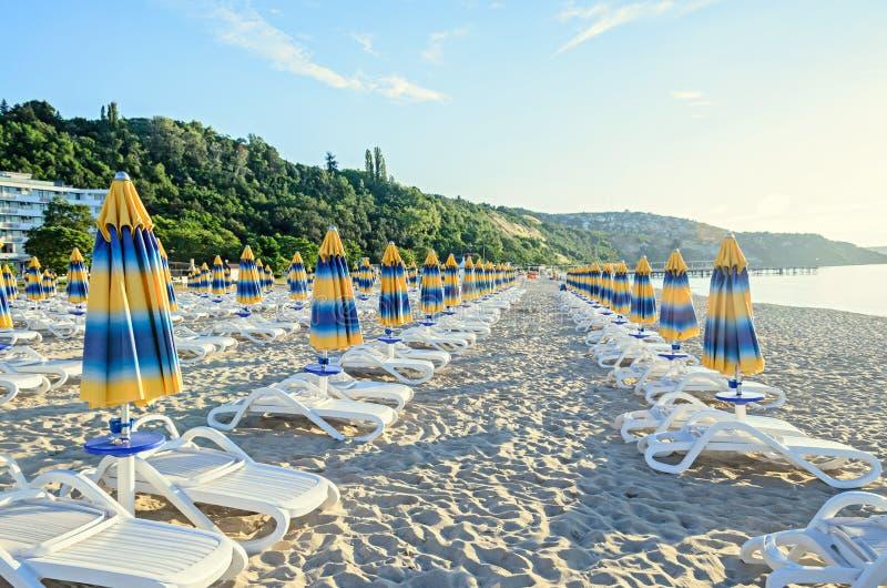Покрашенные обнажанные зонтики солнца, песок пляжа и кровати стоковые фотографии rf