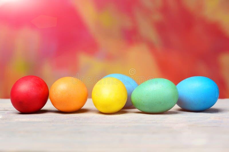 Покрашенные пасхальные яйца в линии или строке на красочной предпосылке стоковые изображения