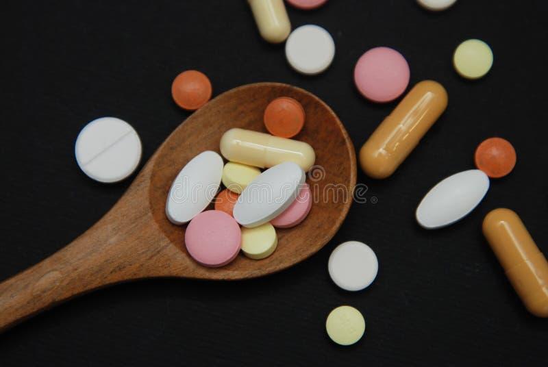 Покрашенные пилюльки в деревянной ложке с частью пилюлек медицины изолированных на черной предпосылке Концепция здоровья и медици стоковые изображения
