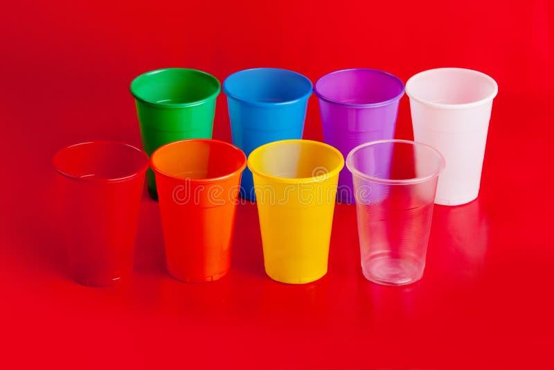 Покрашенные пластичные чашки на красной предпосылке стоковая фотография rf