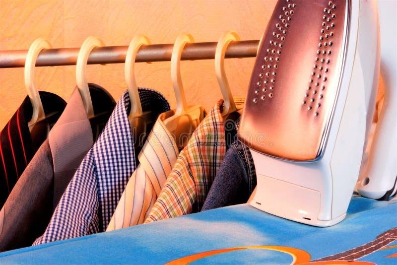 Покрашенные рубашки на вешалке, электрический утюг, утюжа доска в прачечной стоковое изображение rf