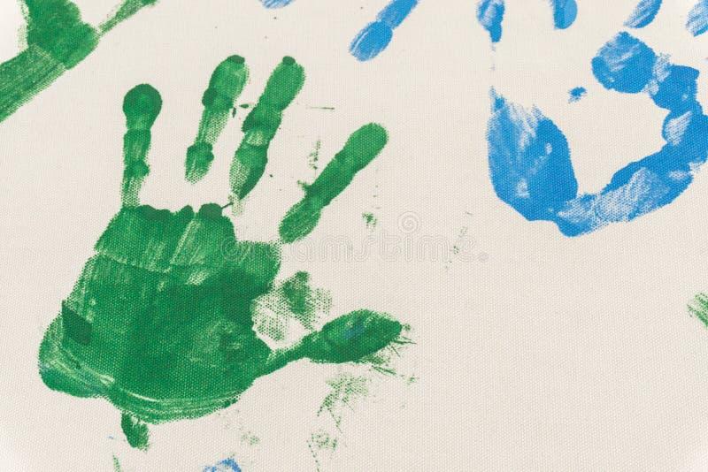 Покрашенные руки, проштемпелеванный на бумаге стоковое изображение