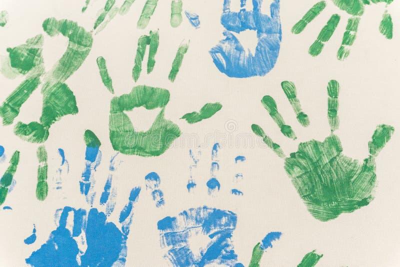 Покрашенные руки, проштемпелеванный на бумаге стоковое фото