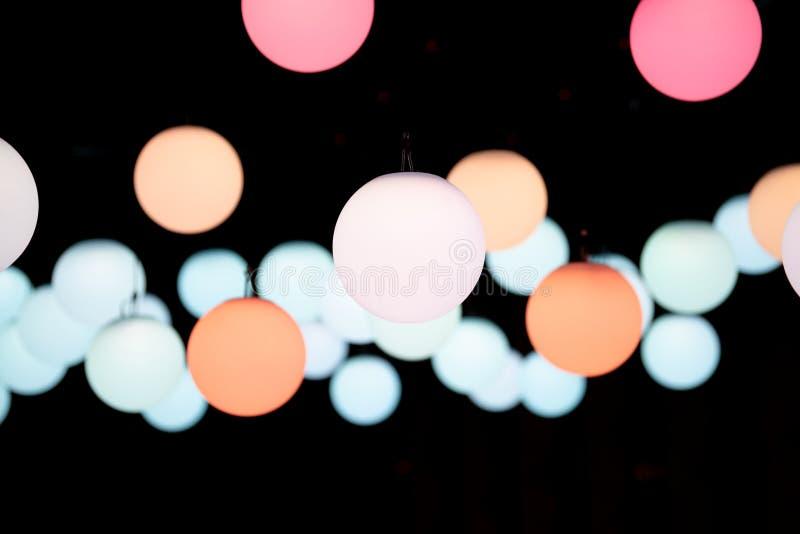 Покрашенные света круглого глобуса привесные приостанавливанные на темном backround стоковые изображения