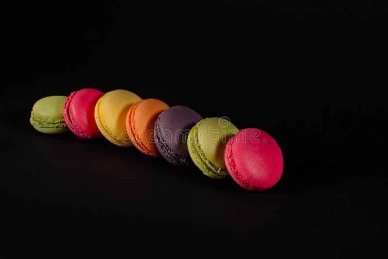Покрашенные macaroons на черной предпосылке стоковое фото