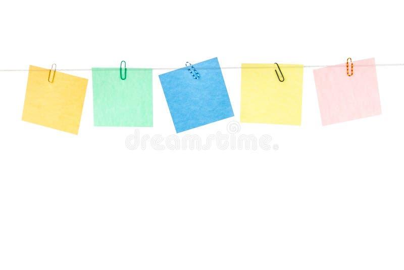 Покрашенный желтые, зеленые, голубые, красные стикеры при бумажные зажимы вися на веревочке стоковые изображения