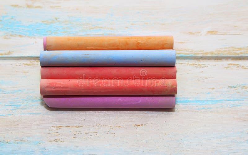 Покрашенный мел для рисовать на белой деревянной предпосылке стоковое фото