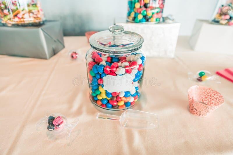 Покрашенный опарник конфеты стеклянный на сладостной таблице бара стоковые изображения rf