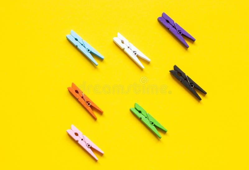 7 покрашенных зажимок для белья в ряд на желтой предпосылке стоковые фотографии rf