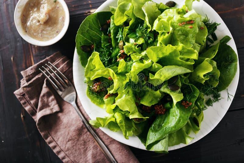 Покройте свежую еду диеты предпосылки семян льна зеленого салата темную деревянную стоковое фото