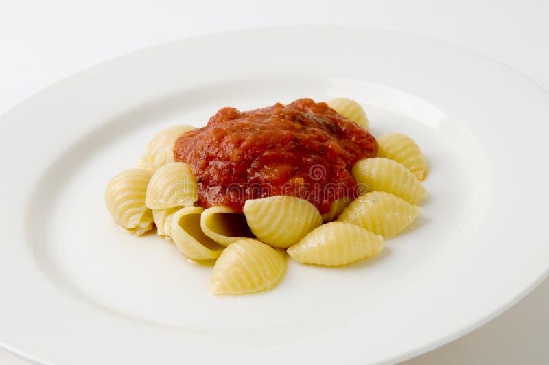 покрынные макаронными изделия красные раковины соуса стоковое фото