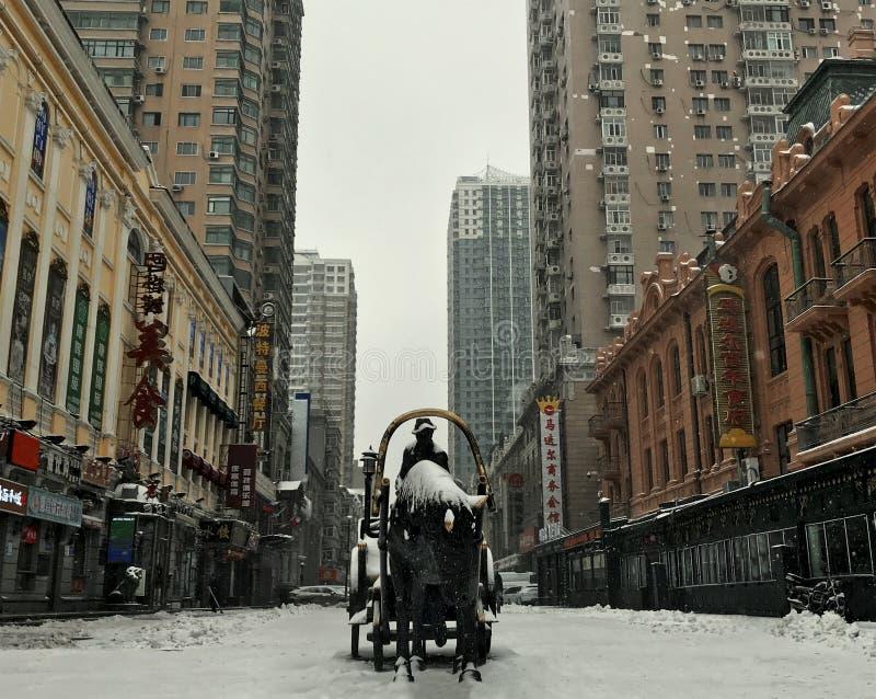 покрытая Снег, современная китайская улица с памятником Лишение памятника с всадником на китайской улице с высотными зданиями стоковые фото