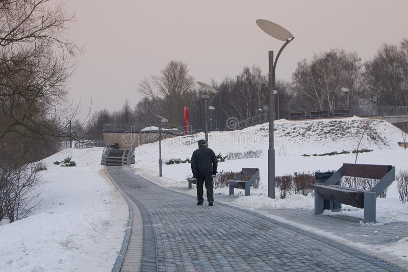 покрытые Снег деревья и стенды в городе паркуют Пожилой человек в парке воссоздания стоковое изображение rf