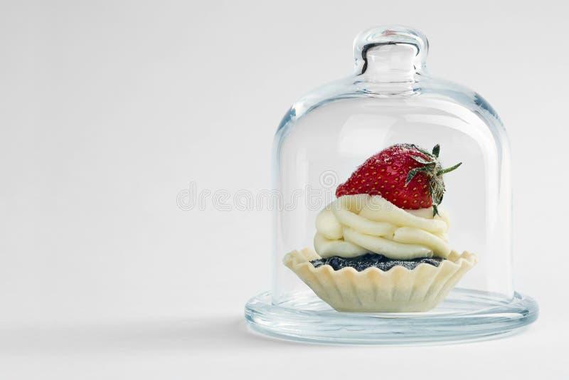 Покрытый с tartlet стеклянного случая на белой предпосылке стоковое изображение
