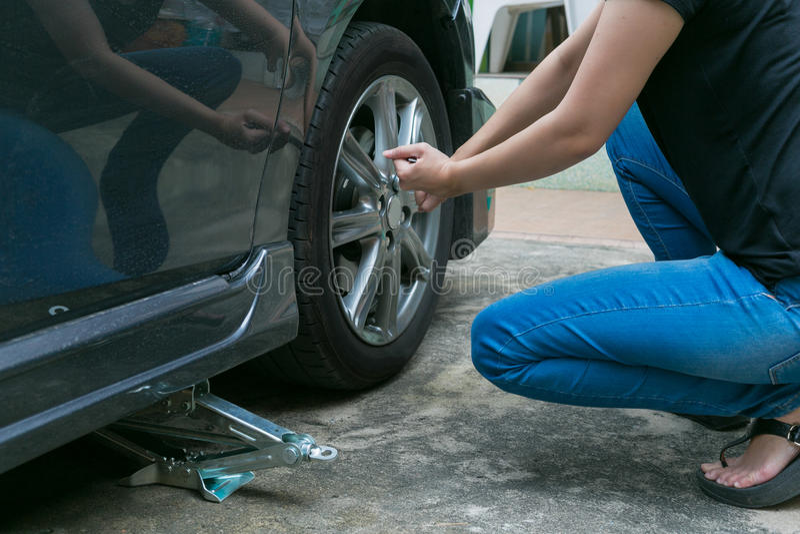 Download Покрышка женского водителя изменяя на ее сломленном автомобиле Стоковое Изображение - изображение насчитывающей вспомогательную, bolls: 81812183