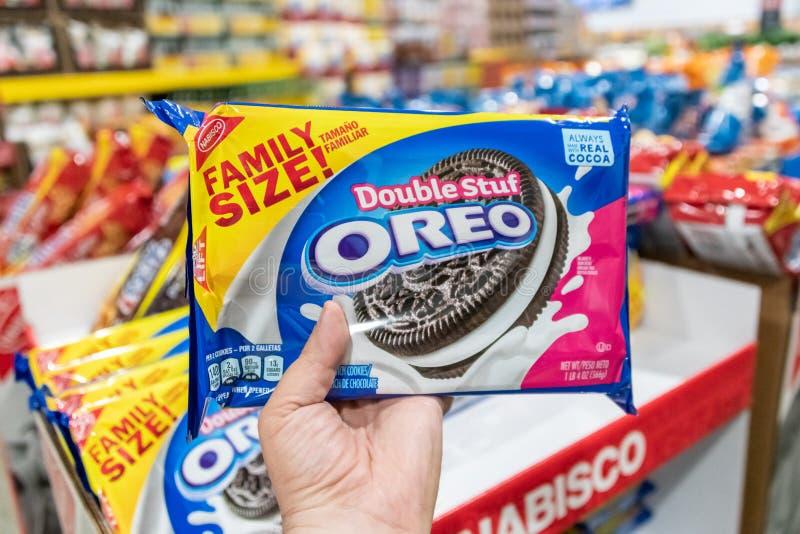 Покупатели вручают удержание пакета размера семьи печений бренда Oreo стоковые изображения rf
