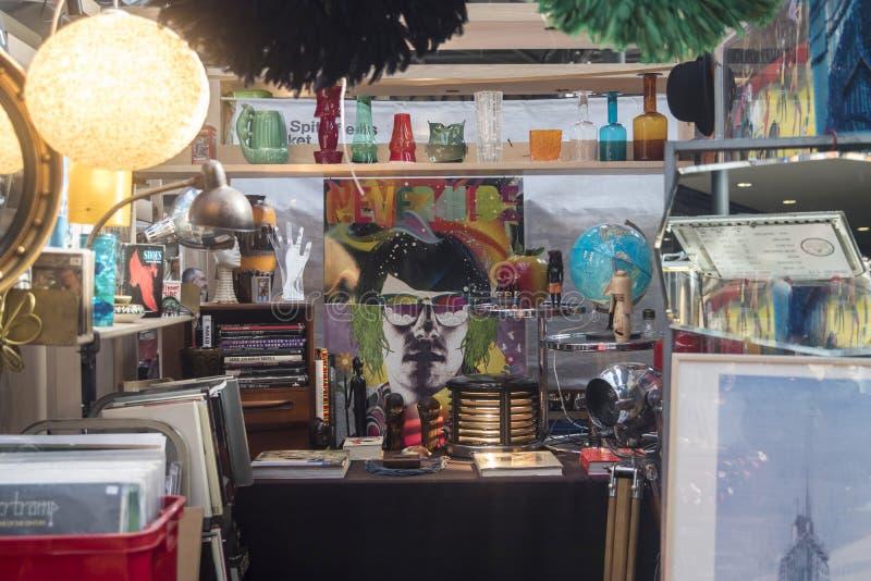 Покупатели на рынке рынка шутовства Spitalfields в-четвертых самая популярная привлекательность в городе привлекая над 100 000 че стоковое изображение