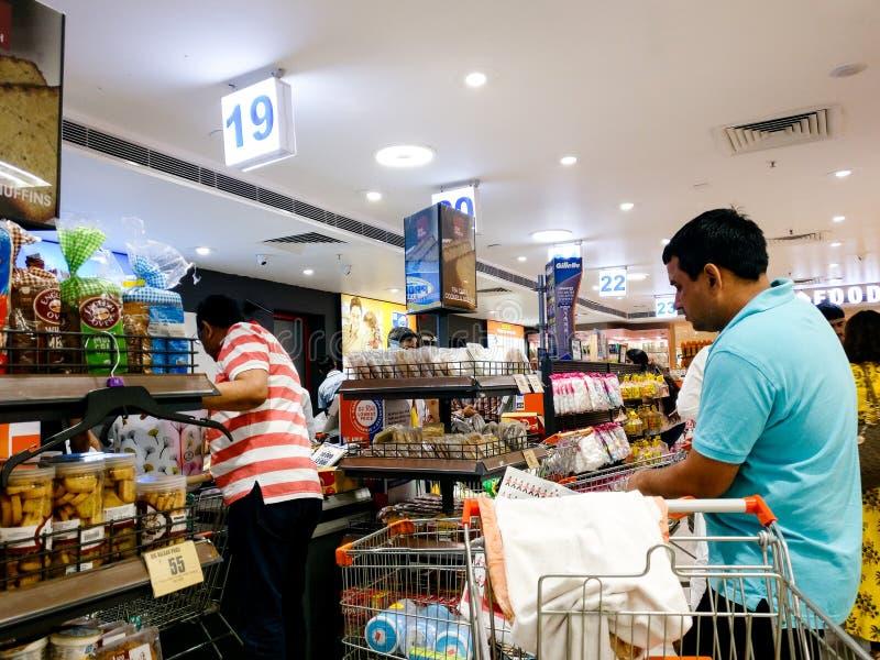 Покупатели стоя, что в линии представить счет и оформить заказ в современном магазине гипермаркета стоковое фото rf