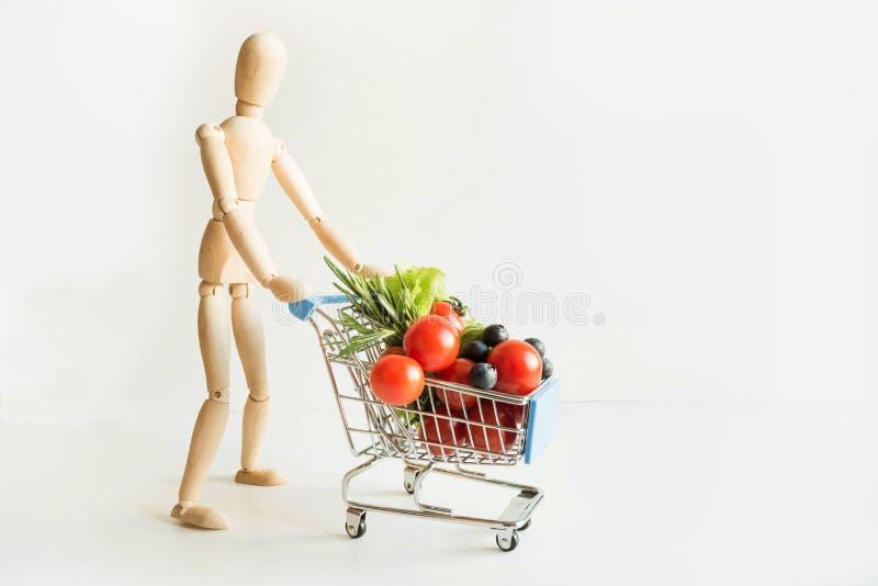 Покупатель как куклы с вагонеткой бакалеи Полная корзина еды Покупки концепции стоковая фотография