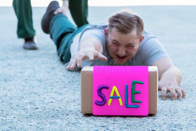 Покупатель молодого человека лежит на тротуаре около магазина и с усилием вытягивает его руку к коробке с продажей надписи стоковые фото