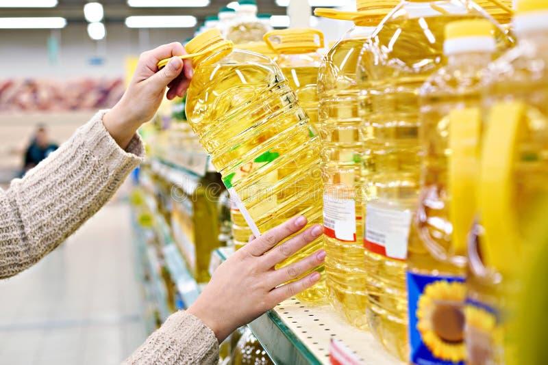 Покупатель принимает подсолнечное масло от полки в магазине стоковые фото