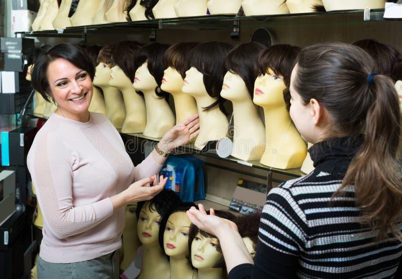 Покупатели обсуждая о синтетических волосах стоковое фото rf