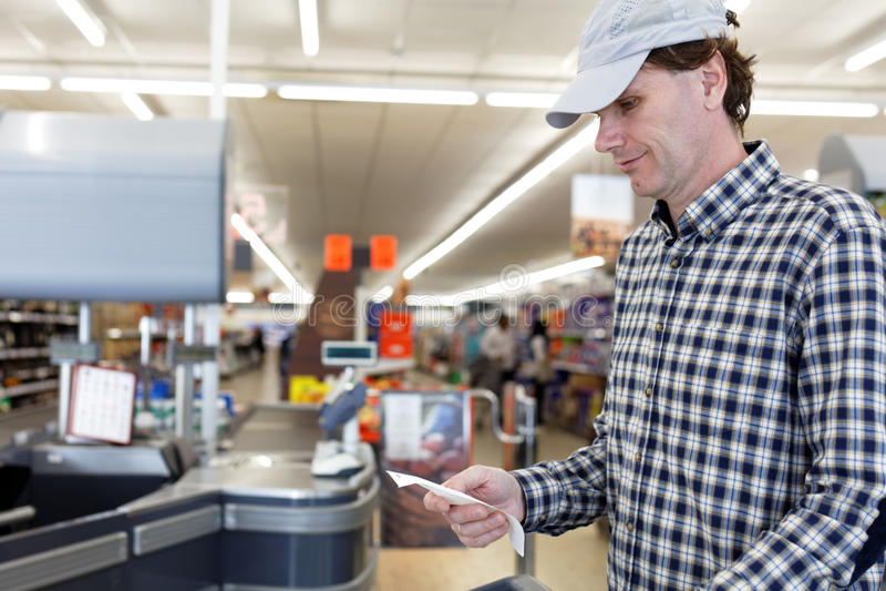 Покупатель проверяет получение наличных денег в супермаркете стоковые фото