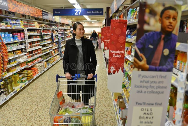 Покупатель просматривает междурядье супермаркета стоковое фото