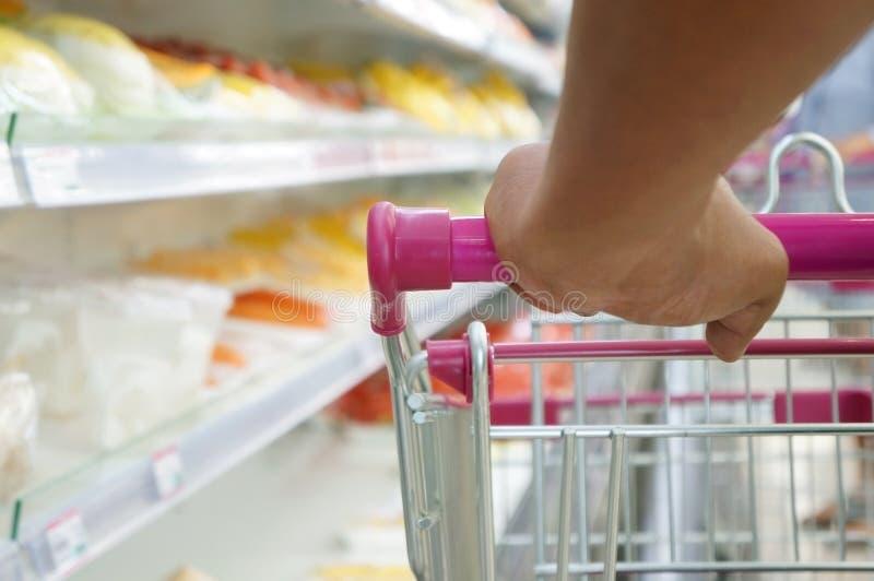 Покупатель с вагонеткой на супермаркете стоковое изображение