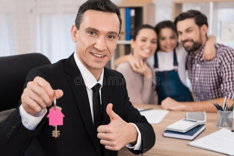 Покупать свойство Радостный риэлтор сделал выгодное предложение для того чтобы купить дом для молодой семьи стоковое фото