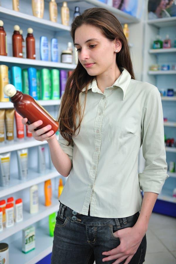 покупая женщина шампуня фармации стоковое фото rf