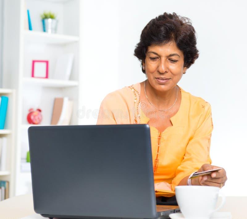 Покупка возмужалой индийской женщины он-лайн стоковое изображение