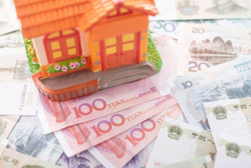 Покупка или арендное концепция дома Близко вверх по нескольким юаней валюты банкноты китайских (CNY или RMB) и модели дома стоковая фотография rf