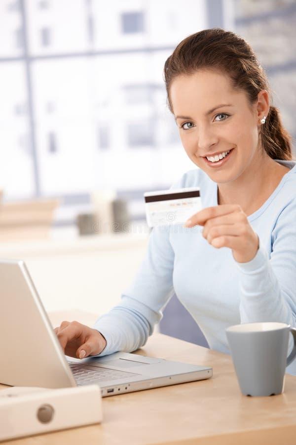 Покупка молодой женщины на усмехаться интернета стоковые фото
