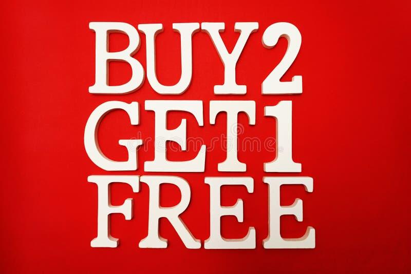 Покупка 2 получает одно свободное продвижение продажи на красной предпосылке стоковые фотографии rf