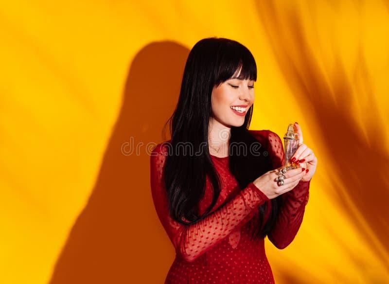 Покупки брюнета духов бутылки тени красного цвета предпосылки женщины покупателя желтые стоковые фото