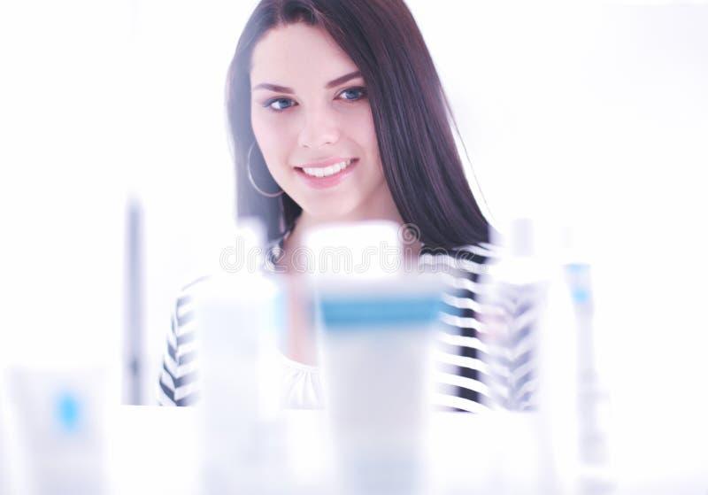 Покупки - бутылка удерживания молодой женщины шампуня в супермаркете стоковое фото rf
