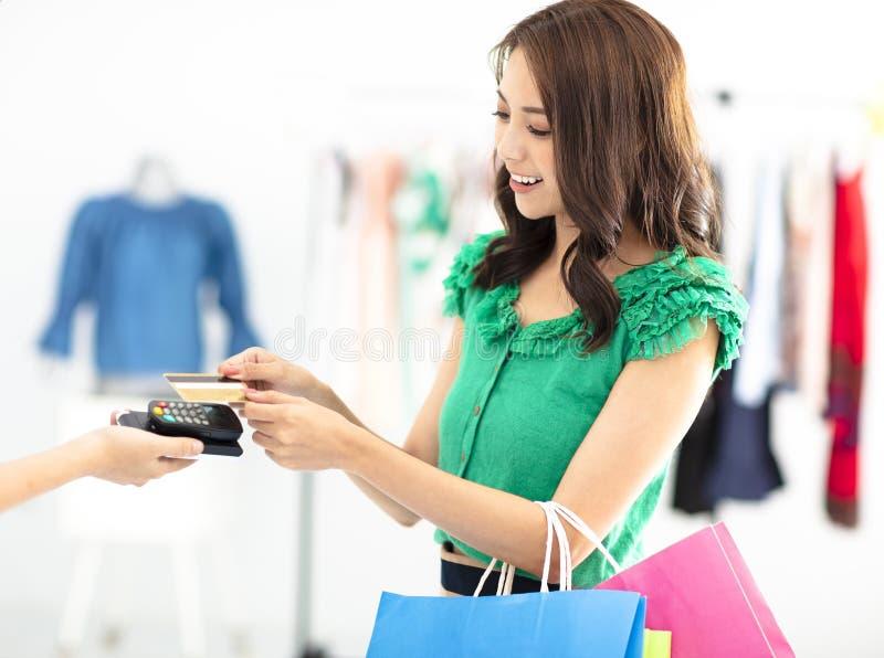 покупки женщины в магазине одежд и оплачивать кредитной карточкой стоковое изображение