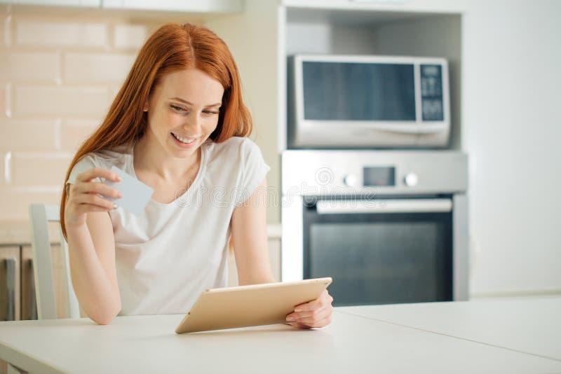 Покупки женщины онлайн используя таблетку и кредитную карточку в кухне стоковая фотография