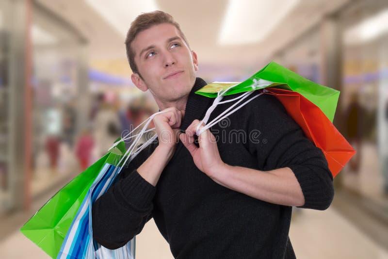 Покупки или приобретение молодого человека в моле смотря вверх стоковое фото rf