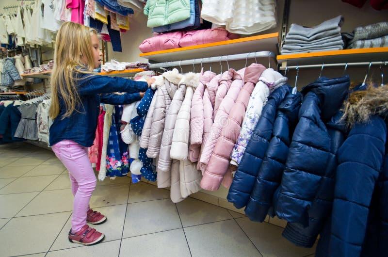 Покупки маленькой девочки для новых одежд стоковое фото rf