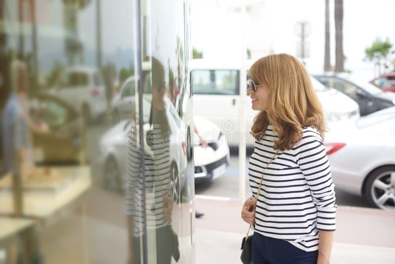 Покупки окна женщины в городе стоковое изображение