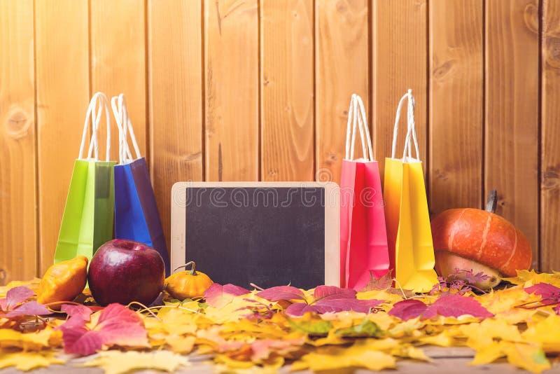 Покупки осени, мода Красочные хозяйственные сумки закрывают вверх Листья осени Хозяйственные сумки, продажа скопируйте космос Кра стоковые фото