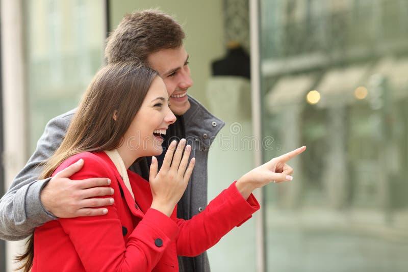 Покупки пар наблюдая в внешней витрине магазина стоковое фото rf