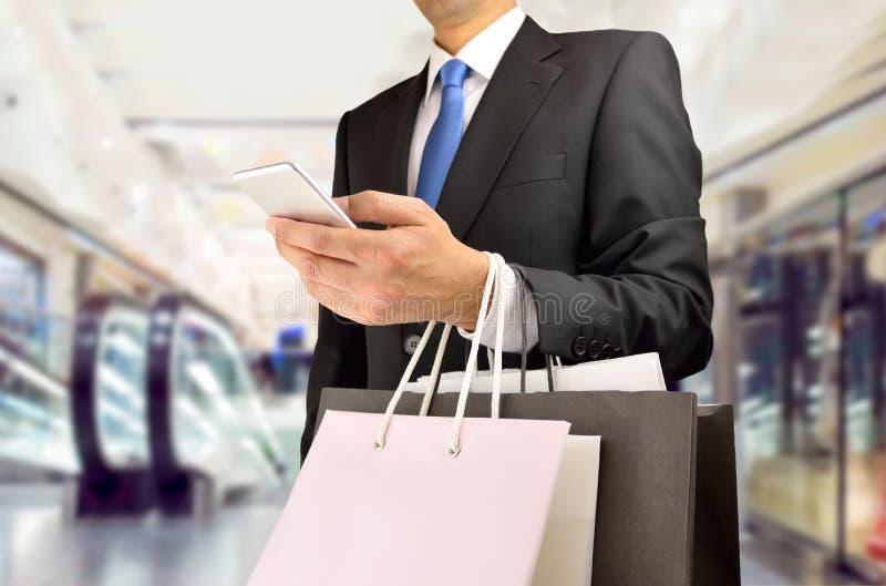 Покупки человека используя мобильный телефон стоковые изображения