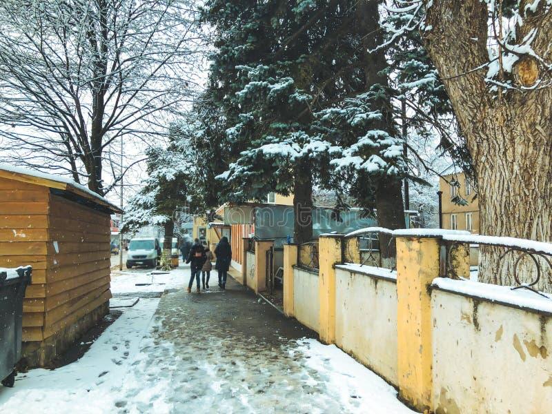 Полдень зимы Люди идут в снег Улица Snowy Лыжный курорт Bakuriani горы стоковое фото